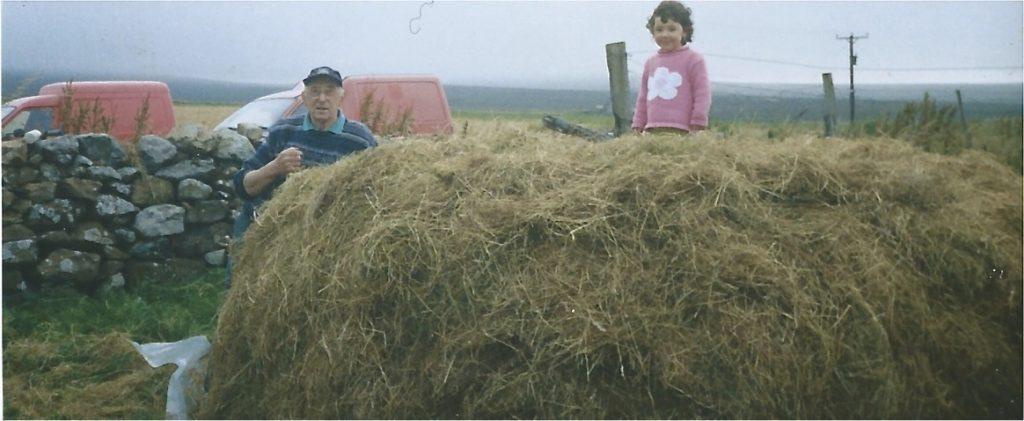 an elderly crofter works the hay